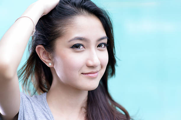 Beautiful asian girl running her hand through her hair stock photo