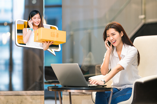 istock Beautiful Asian girl shop online using phone call with female small business owner delivering parcel box. Internet shopping lifestyle, Ecommerce, shipment service, SME sale promotion advertise concept 881882616