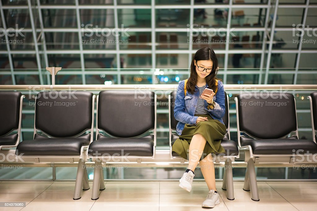 Beautiful asian girl smiling at smartphone, waiting to board airplane stock photo