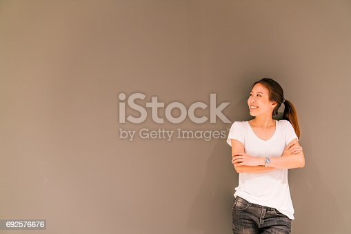 istock Beautiful Asian girl standing on grey wall background, looking at copy space 692576676