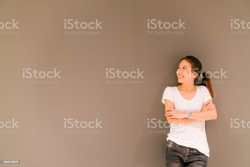 Beautiful Asian girl standing on grey wall background, looking at copy space stock photo