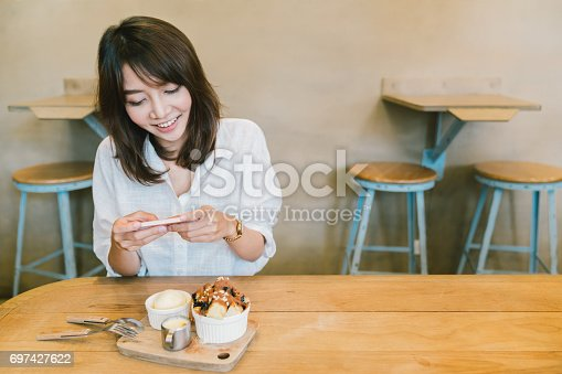 istock Beautiful Asian girl taking photo of chocolate toast cake, ice-cream, and milk at coffee shop. Dessert or food photograph hobby. Smartphone or mobile phone photography habit concept. With copy space 697427622