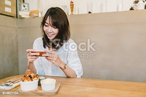 istock Beautiful Asian girl taking photo of chocolate toast cake, ice-cream, and milk at coffee shop. Dessert or food photograph hobby. Smartphone or mobile phone photography habit concept. With copy space 914621134