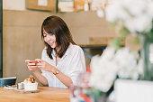 美しいアジアの女の子は甘いデザート、喫茶店、ソーシャル メディアに掲載、スマート フォンのカメラを使用しての写真を撮影。食品写真趣味、カジュアルなリラックス ライフ スタイル、現代の社会的ネットワークの習慣の概念