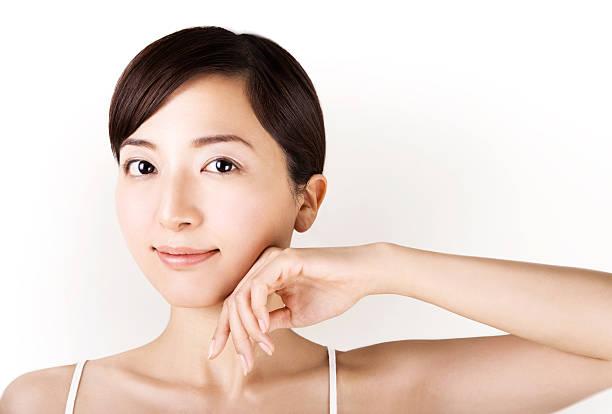 美しいアジアの女性は彼女の顔に触れ白で分離 ストックフォト