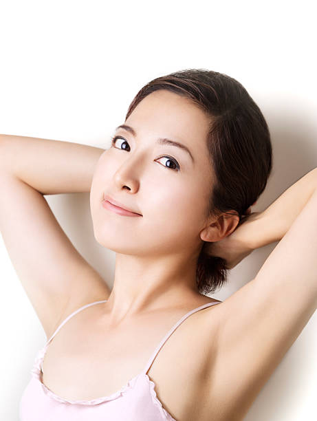 Belle fille asiatique, toucher ses cheveux.  Souriant à la caméra - Photo