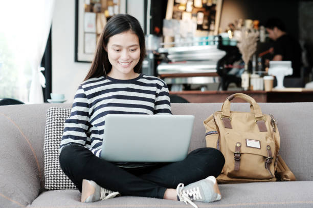 Beautiful asian girl using laptop computer while sitting on sofa with smiling face emotion, people and technology concept, lifestyle stock photo