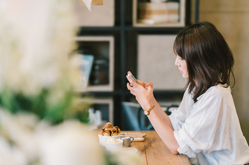 Beautiful Asian girl using smartphone at cafe with chocolate toast, ice cream, and milk syrup. Coffee shop dessert and modern casual lifestyle or mobile phone technology concept. With copy space