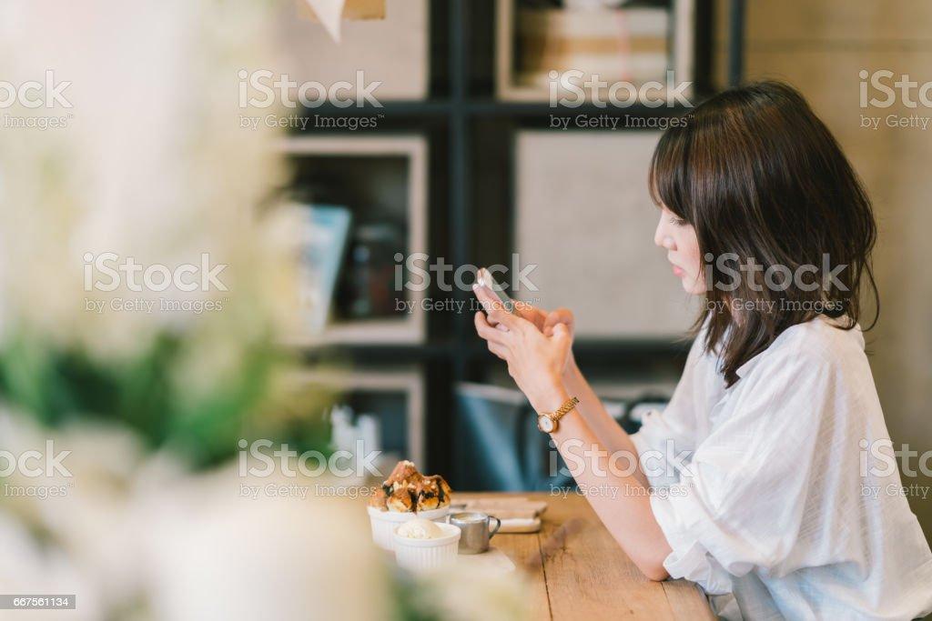 Beautiful Asian girl using smartphone at cafe with chocolate toast, ice cream, and milk syrup. Coffee shop dessert and modern casual lifestyle or mobile phone technology concept. With copy space stock photo