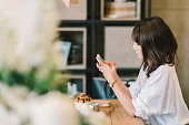 チョコレート トースト、アイスクリーム、ミルク シロップとカフェでスマート フォンを使用して美しいアジアの少女.コーヒー ショップ デザートとモダンなカジュアルなライフ スタイルや携帯電話技術コンセプト。コピー スペース