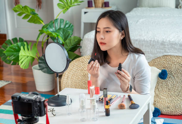 A beautiful Asian girl who is a beauty blogger is reviewing products online via social cam. Online sales, online business, technology for selling products stock photo