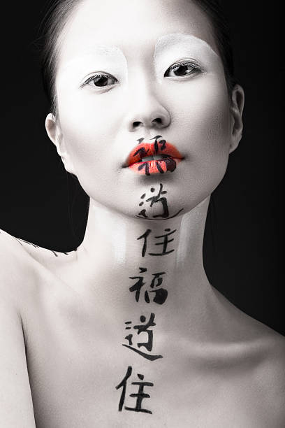 beautiful asian girl with white skin, red lips and hieroglyphics - geisha girl stock photos and pictures