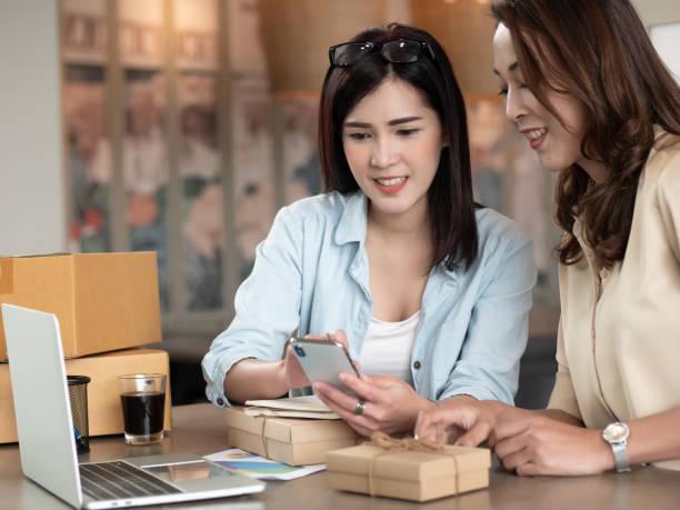 Empresario de PYMES freelance trabajo de hermosa chica asiática PYME, negocio familiar. Ella es el uso del teléfono con la caja en casa. Microempresaria, online marketing caja y entrega concepto de envasado. - foto de stock