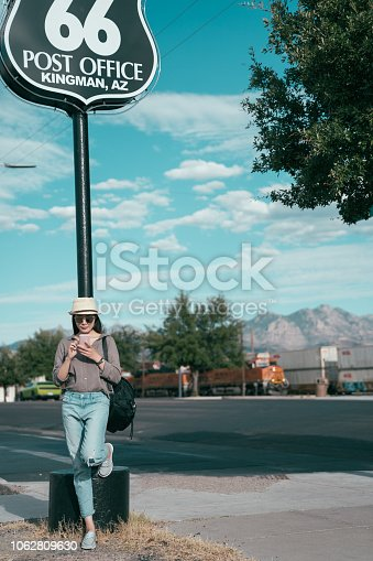 full length of a beautiful asian local woman living in kingman and waiting for her internet friend under the famous route 66 sign. young lady with straw hat using cell phone rely on the landmark.