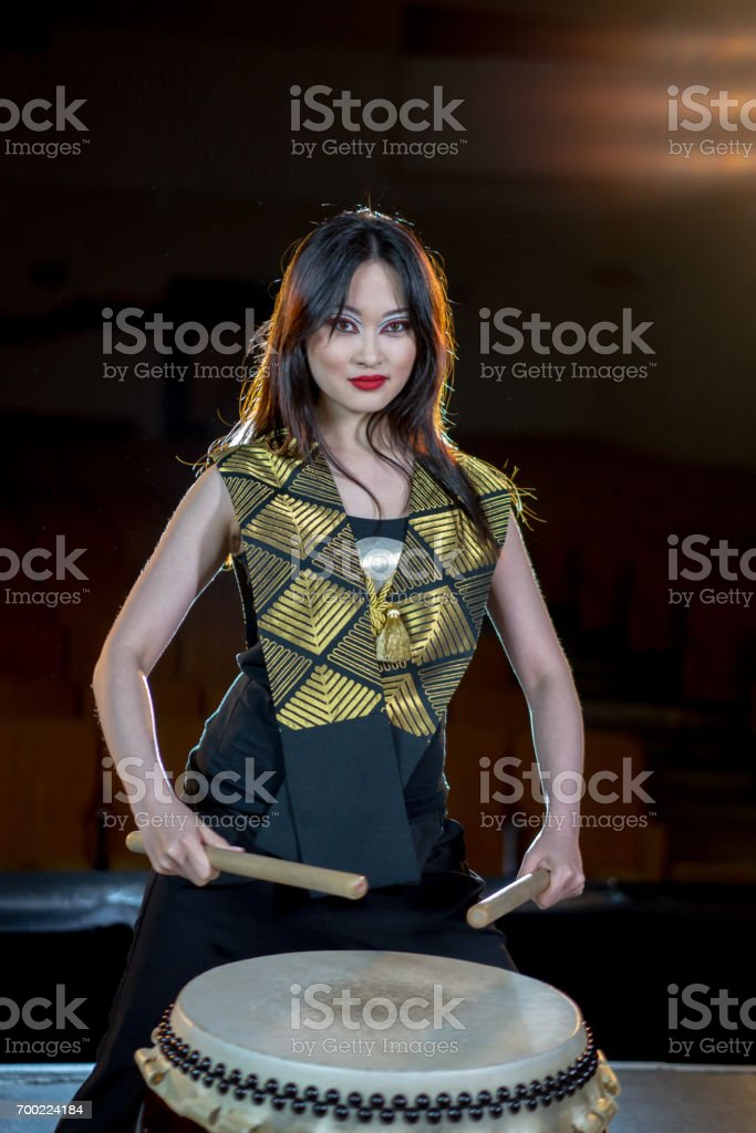 beautiful asian long haired drummer girl with drumsticks, studio shot on a dark background. stock photo
