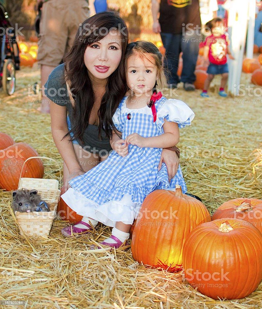 Beautiful Asian Mother and Daughter at a Halloween Pumpkin Patch stock photo