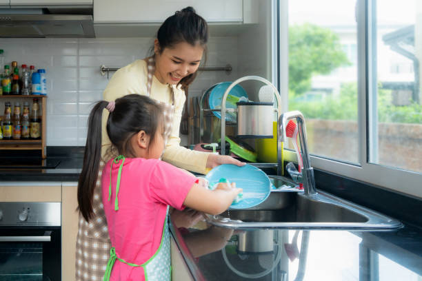 Beautiful Asian mother and daughter having fun while washing dishes together with detergent on sink in kitchen at home. Happy family time to teaching daughter to housework. Beautiful Asian mother and daughter having fun while washing dishes together with detergent on sink in kitchen at home. Happy family time to teaching daughter to housework. chores stock pictures, royalty-free photos & images