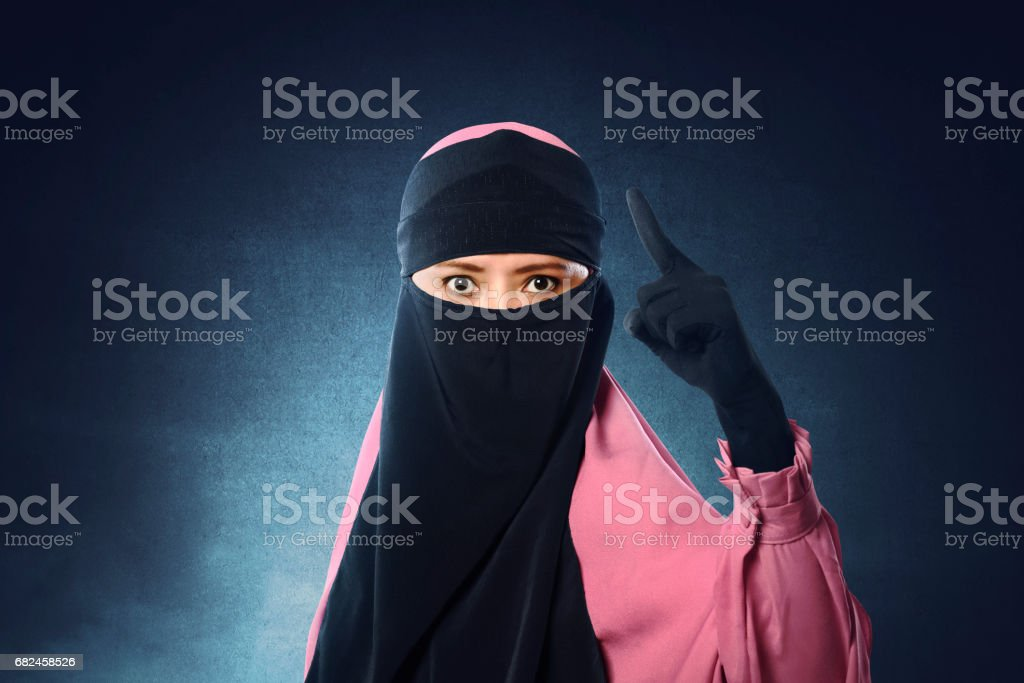 Beautiful asian muslim woman in veil pointing with upset eyes royalty-free stock photo
