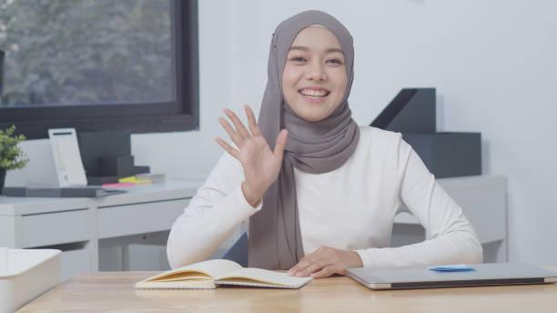 Hermosa mujer musulmana asiática hablando con la cámara, atractiva mujer musulmana asiática sonriendo VideoConferencia, Mujer musulmana moderna del estilo de vida de la región del sudeste y asia oriental - foto de stock
