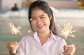 Beautiful Asian schoolgirl is playing fireworks in a public garden. Thai children in white school uniform carrying fireworks in their hands.