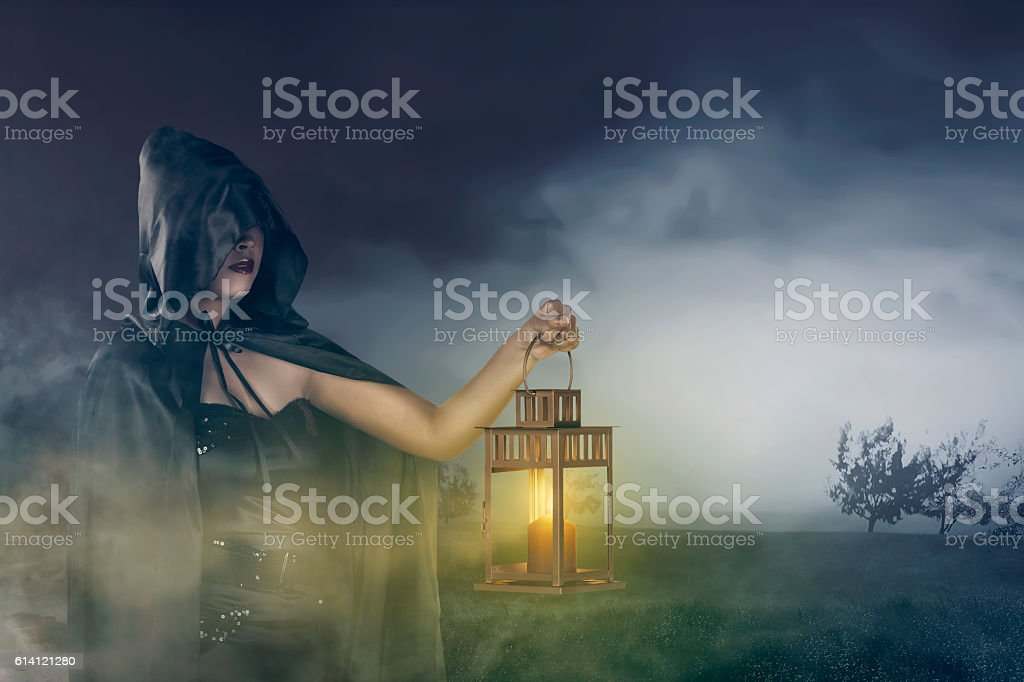 Beautiful asian witch girl holding a lantern with a cloak stock photo