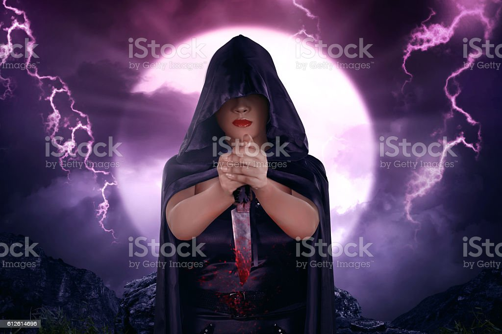 Beautiful asian witch with black cloak holding bloody knife stock photo