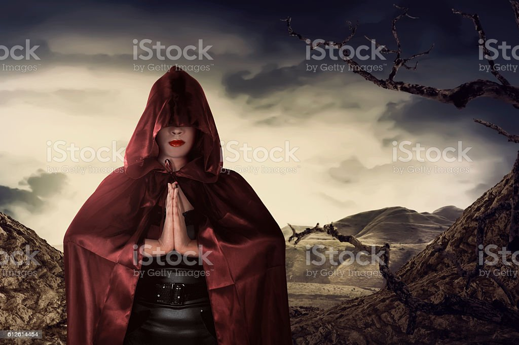 Beautiful asian witch woman with red cloak praying stock photo