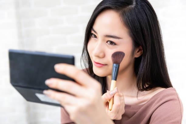 schöne asiatische frau beauty blogger tun make-up tutorial - gesicht make up anleitungen stock-fotos und bilder