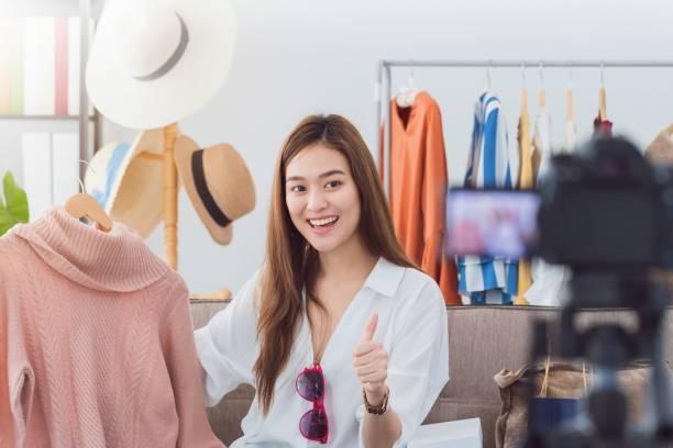 schöne asiatische bloggerin zeigt einkaufskleidung und kleid. vor der kamera, um vlog video-live-streaming zu hause aufzunehmen. business online influencer on social media concept. - dresses online shop stock-fotos und bilder