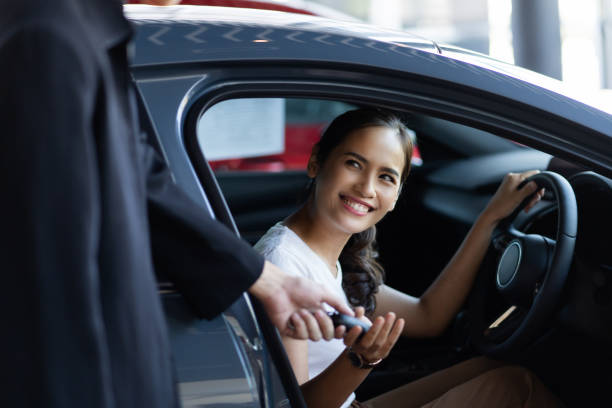 Beautiful asian woman buying a car at the showroom stock photo