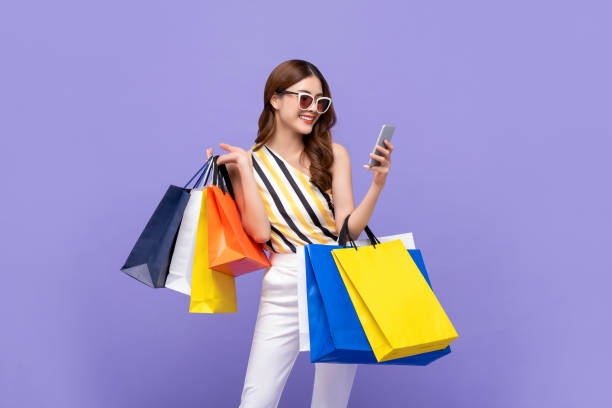 Beautiful Asian woman carrying colorful bags shopping online with mobile phone stock photo