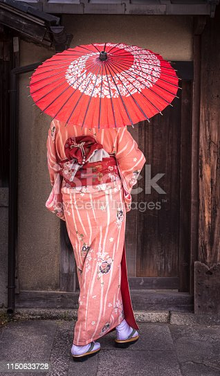 Beautiful woman is dressed-up in her ornate kimono, and is going for a walk around the famous Gion District of Kyoto, Japan. Shot in Spring on the streets of Kyoto in front of a non-descript door.