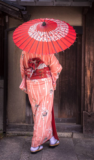 Beautiful Asian woman dressed in her Kimono with parasol in Kyoto, Japan stock photo