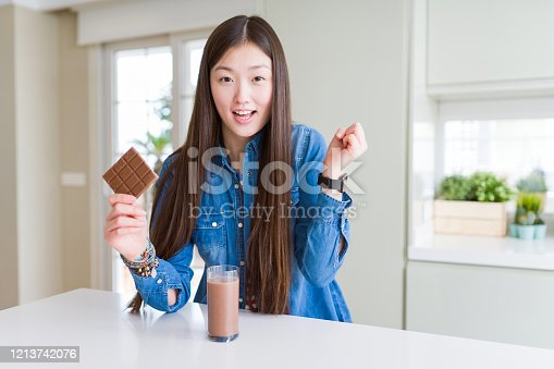 Beautiful Asian woman drinking chocolate milkshake and holding chocolate bar screaming proud and celebrating victory and success very excited, cheering emotion