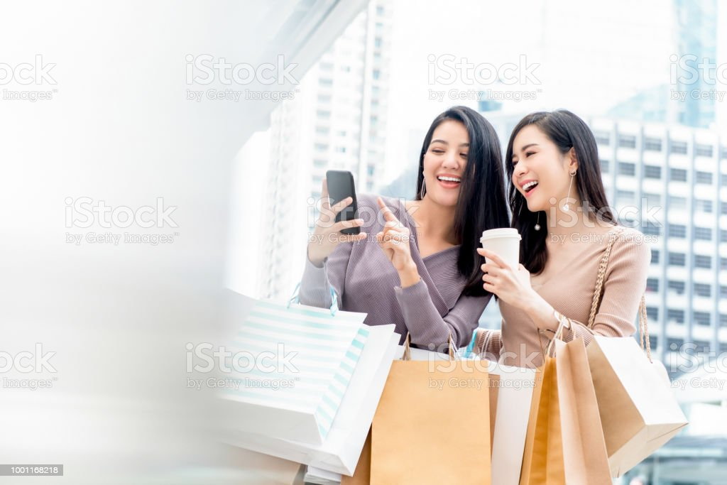 Beautiful Asian woman friends using smartphone while shopping in the city stock photo
