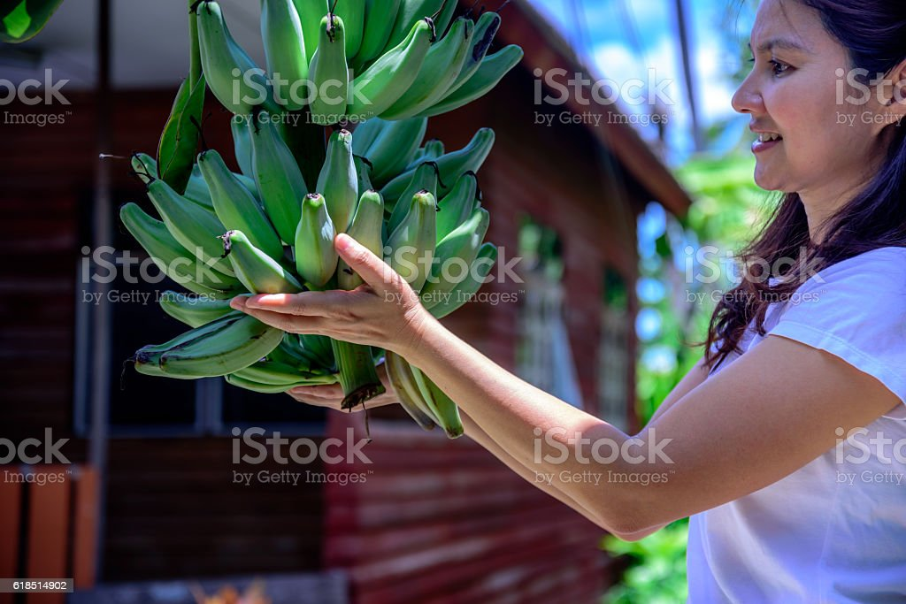 Beautiful asian woman holding bunch of banana at home stay stock photo