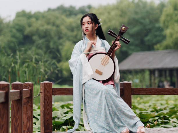 Beautiful Asian woman in cyan costume clothes hanfu holding yueqin (four stringed plucked instrument) with lotus pond background in rainy day, traditional ancient Chinese beauty, time travel fiction. stock photo