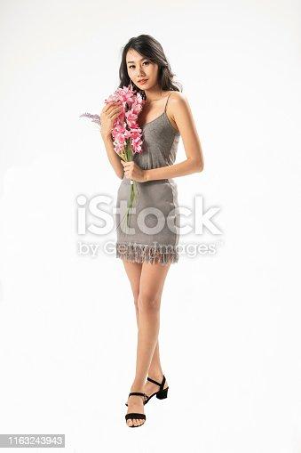 Beautiful Asian woman in grey dress on white background studio shot.