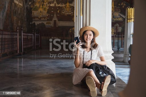 Beautiful Asian woman in  white dress and straw hat sitting on  Wat Phra Kaew Temple pavilion floor with backpack, holding cellphone on hand and camera on lap, travel and vacation concept.