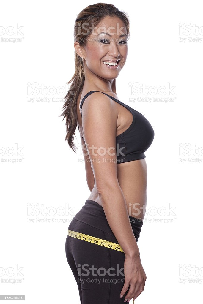 Beautiful asian woman is measuring her hips stock photo