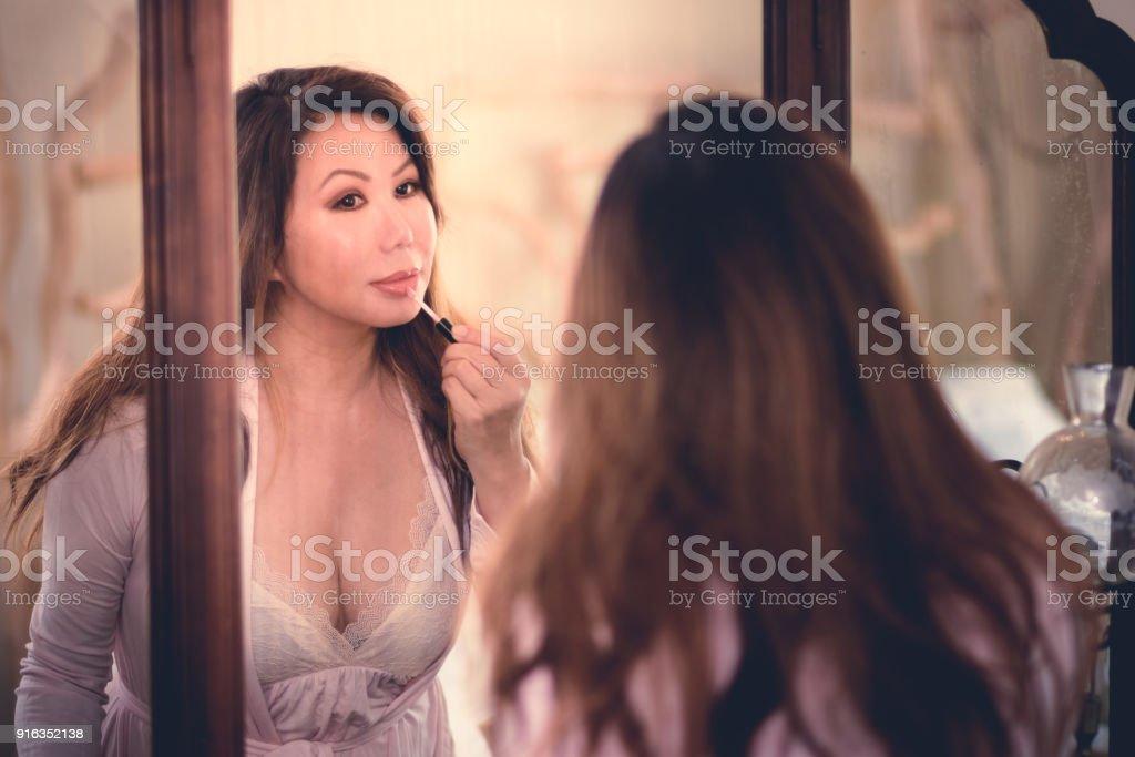 Beautiful Asian woman looking in vintage mirror applying lip gloss stock photo