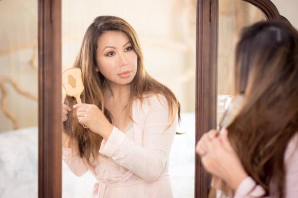 Beautiful Asian woman looking in vintage mirror brushing hair stock photo