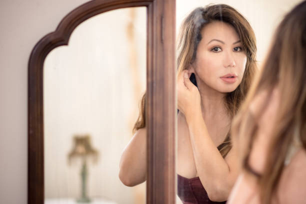 Beautiful Asian woman looking into antique mirror putting in earrings stock photo