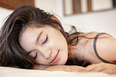 istock Beautiful asian woman lying on the bed with pajamas and eyes closed 1034746550
