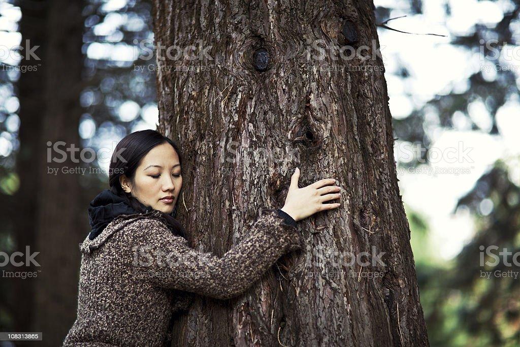beautiful asian woman outdoor huging a tree royalty-free stock photo