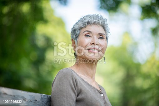 A beautiful senior woman of asian descent spends time  in a park one afternoon. She is sitting on a park bench smiling.
