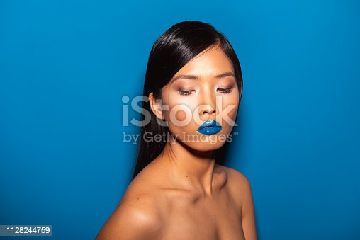 Asian female model posing in front of the blue background.