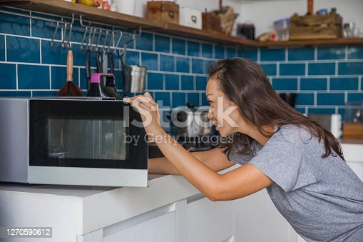 Side shot of a beautiful Asian woman opening her microwave to checking her meals that reheated.