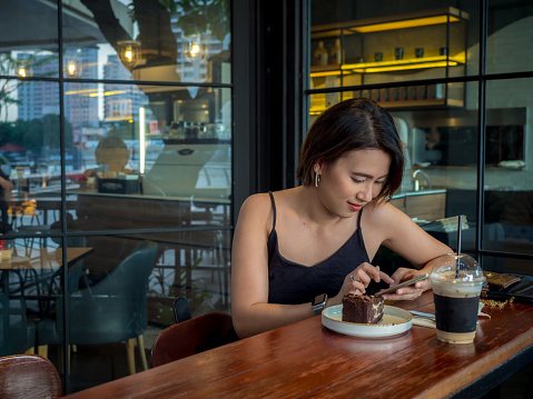 Beautiful Asian woman short hair using smartphone and drinking coffee and dessert at cafe.