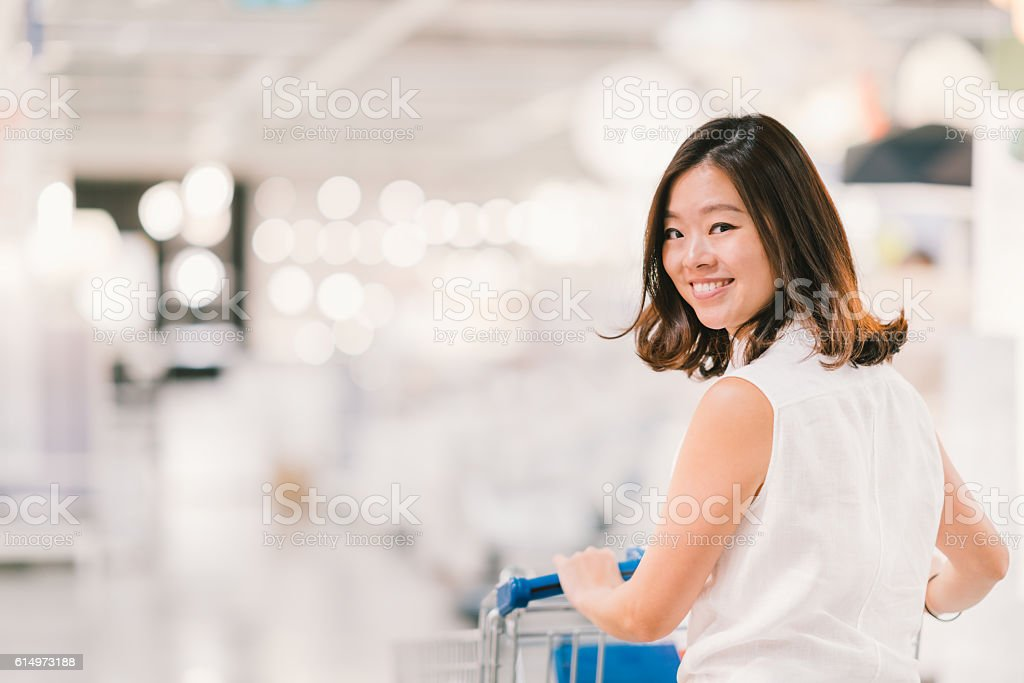 Beautiful Asian woman smiling, with shopping cart stock photo